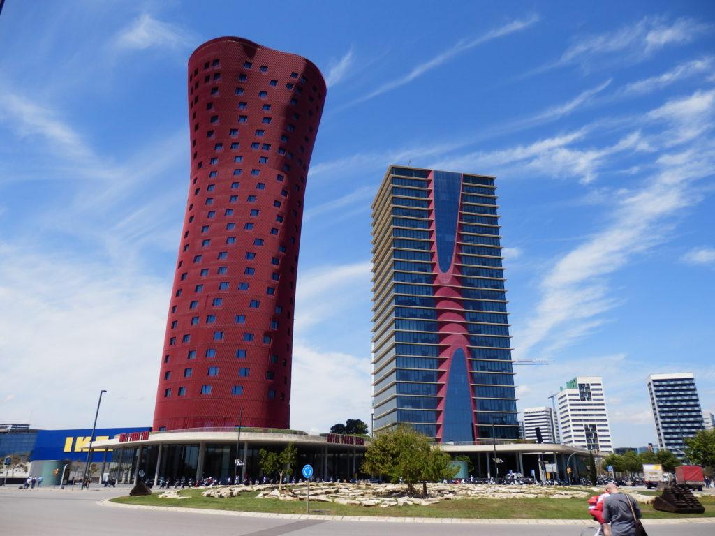Hotel-Türme von Toyo Ito, rund-verformt in rot links, rotes gegabeltes Element vor grauer Fassade rechts