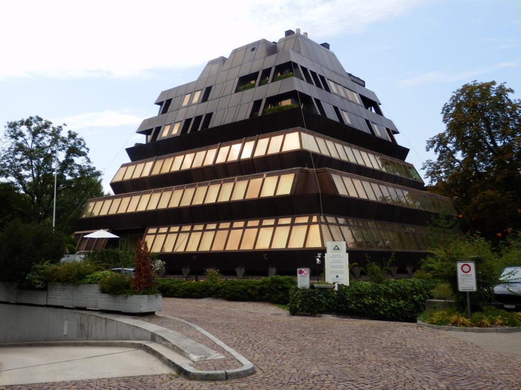 Gebäude in Form eines Pyramidenstumpfes. Fassadenbekleidung in Corten-Stahl, Sonnenschutz-beschichtete Fenser in umlaufenden Fensterbändern