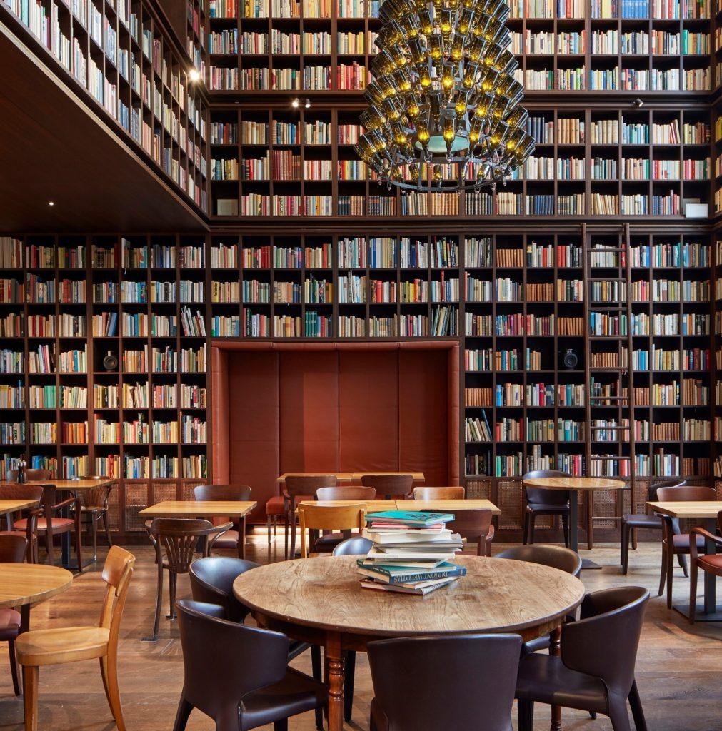 2-Geschoss hohe Bibliothek mit raumhohen Bücherregalen und Kronleuchter aus Weinflaschen.
