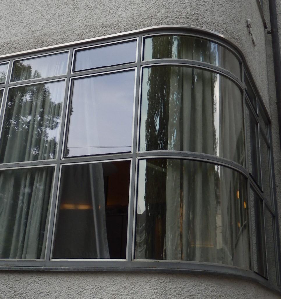 Übereck-Fenster des Hallenbades, gekrümmte Glasscheiben in Metallrahmen.