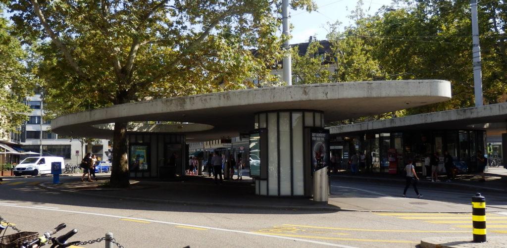 Tram-Pavillon mit runden Kiosken und amorpher Deckenplatte (Beton) und ausgespartem Bereich durch dem ein Baum wächst.